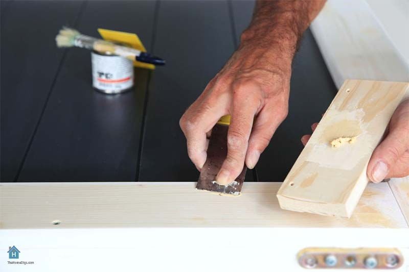 wood worker applying filler to the wood with putty knife
